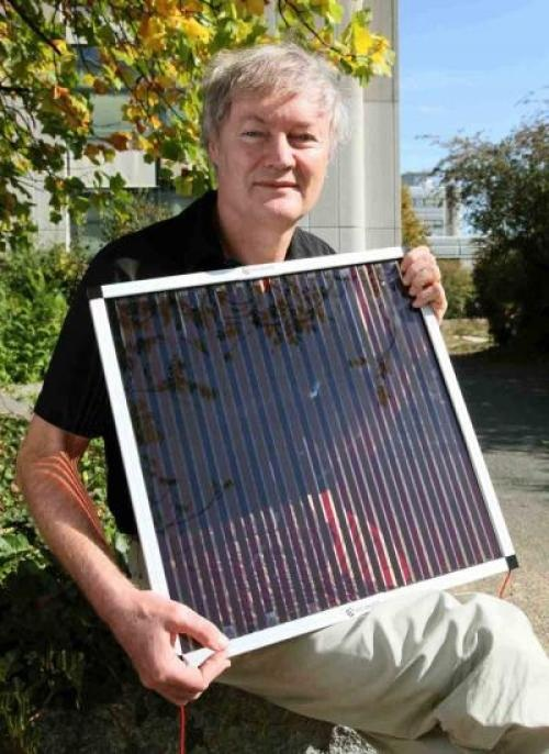 """Michael Grätzel holding one of his dye-sensitized solar cells."" Image Credit: © Alain Herzog/EPFL"